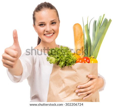 Cheerful woman showing thumb up and holding shopping bag full of fresh food on white background. - stock photo