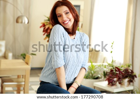 Cheerful woman sitting at home - stock photo