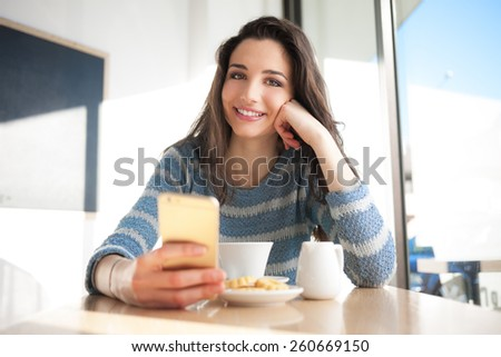 Cheerful woman social networking with her smartphone at the cafe - stock photo