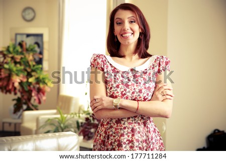 Cheerful woman standing with arms folded at home - stock photo