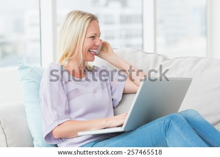 Cheerful woman talking on mobile phone while using laptop on sofa in living room - stock photo
