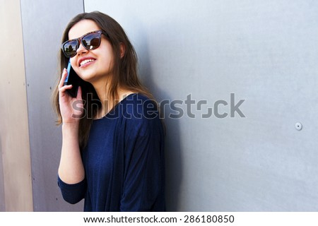 Cheerful woman talking on the phone in the street casual outfit - stock photo