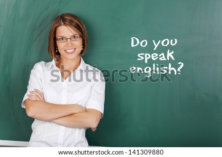 Cheerful woman teaching English class at the classroom - stock photo