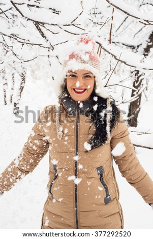 Cheerful woman  tossing snow in the park and having fun - stock photo
