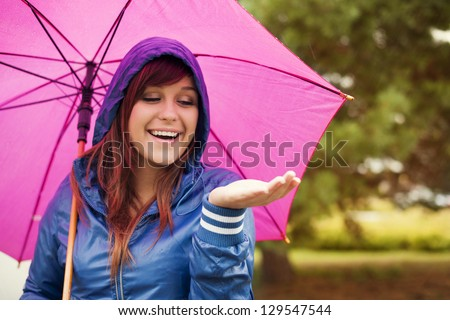 Cheerful woman under pink umbrella checking for rain