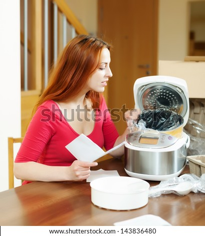 cheerful woman unpacking and reading manual for new crockpot at home interior - stock photo