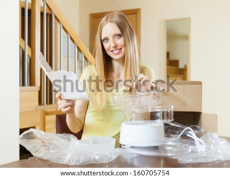 cheerful woman unpacking and reading user manual for new electric steamer at home