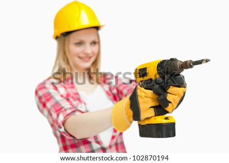 Cheerful woman using an electric screwdriver against white background