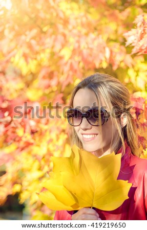 Cheerful woman with autumn leaves in her hands in autumn park - stock photo