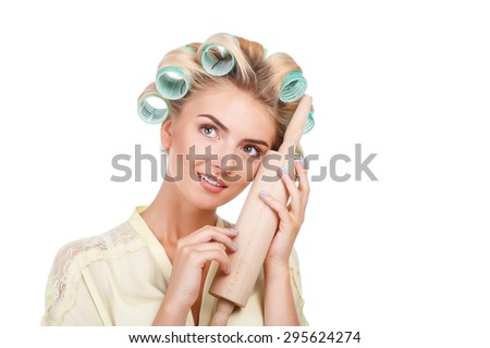 Cheerful woman with curlers in hair is dreaming about her life. She is touching rolling pin to her face gently and smiling. The lady is looking up. Isolated on background and copy space in right side - stock photo