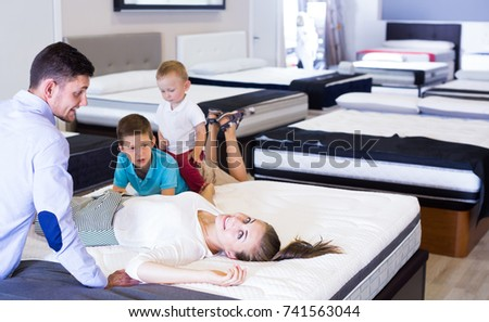 Cheerful woman with her family lying on back on mattress in store in search of right