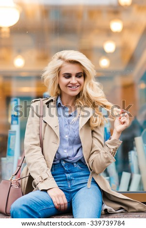 Cheerful woman with luxury blonde hair posing while sitting near shop window, happy female with charming smile enjoying good day during her weekend, beautiful girl relaxing after walking outdoors  - stock photo