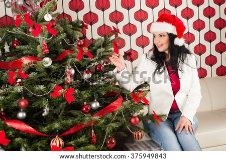 Cheerful woman with natural Chrismas tree touching ribbon