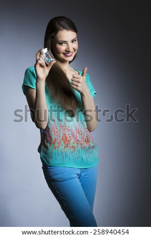 Cheerful woman with pill container showing ok gesture - stock photo