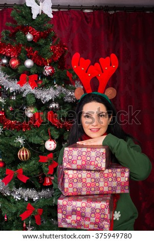 Cheerful woman with reindeer ears holding stack of Christmas presents