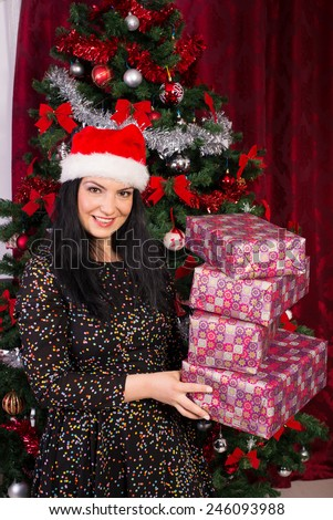 Cheerful woman with santa hat holding Christmas gifts - stock photo