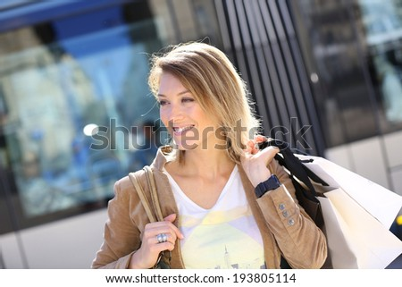 Cheerful woman with shopping bags in town - stock photo