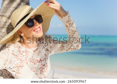 Cheerful woman with summer hat standing under palm tree on tropical beach