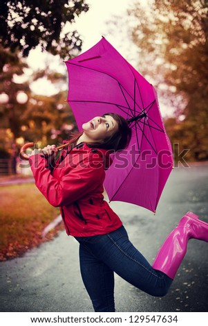 Cheerful woman with umbrella and rubber boots in the rain - stock photo