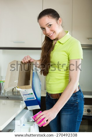 Cheerful woman with washing detergent doing laundry at home  - stock photo