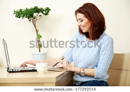 Cheerful woman working at home - stock photo