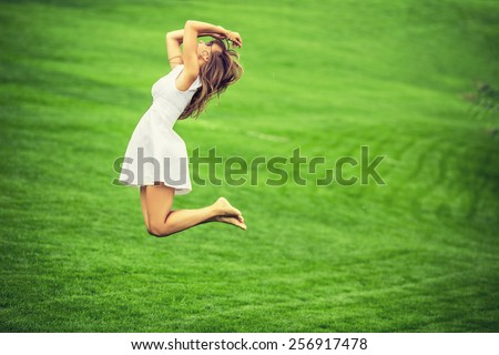 Cheerful woman. Young happy woman jumping with her arms up on a green grass lawn. Attractive woman cheering and enjoying the freedom on a sunny day.  - stock photo
