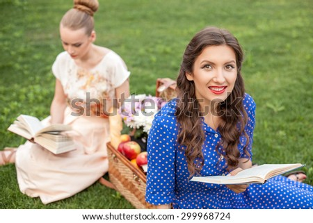 Cheerful women are reading books with concentration. They are sitting on green grass near a basket of food. The brunette lady is looking at the camera and smiling with pleasure - stock photo