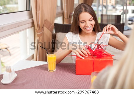 Cheerful women are sitting opposite each other in restaurant. One lady is opening a gift from her friend. She is looking at it with curiosity and smiling. Copy space in left side - stock photo
