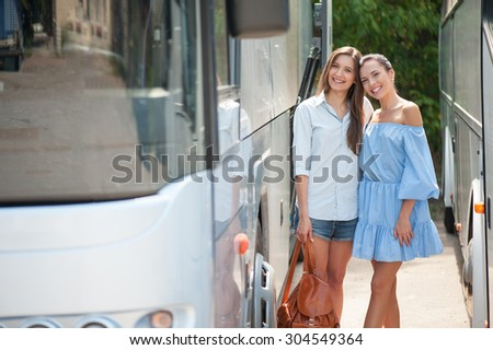 Cheerful women are standing between two buses and waiting for its departure. They are ready for traveling. The girls are embracing and smiling - stock photo
