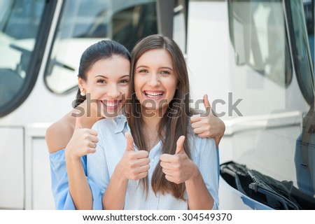 Cheerful women are standing near a bus. They are giving thumbs up and smiling. The friends are embracing. They are waiting for bus departure - stock photo