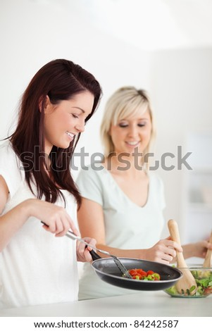 Cheerful Women cooking dinner in a kitchen
