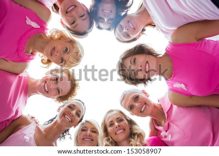Cheerful women in circle wearing pink for breast cancer and smiling at camera on white background