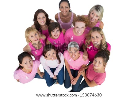 Cheerful women looking up wearing pink for breast cancer on white background - stock photo