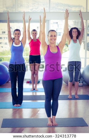 Cheerful women with arms raised in fitness studio on exercise mat - stock photo