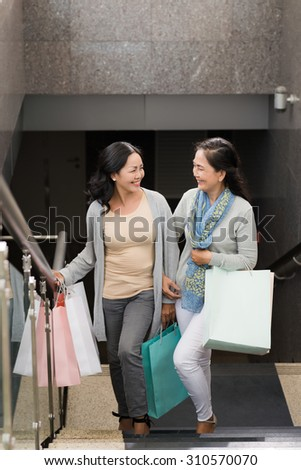Cheerful women with shopping bags going upstairs