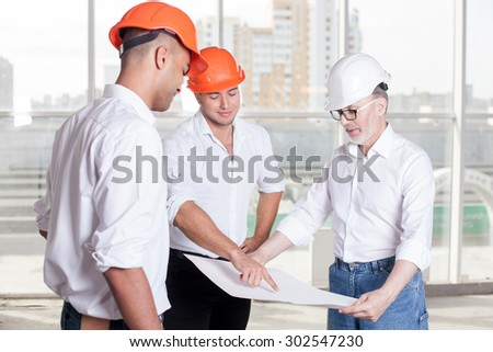 Cheerful workers are planning to build a construction. Senior architect is holding a blueprint. The foreman is pointing his finger at it. The men are looking at the paper and smiling - stock photo