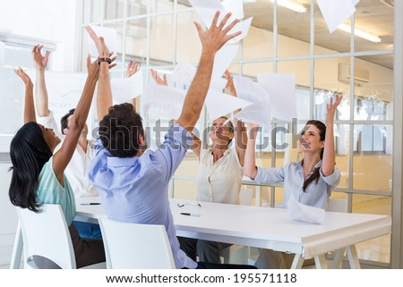 Cheerful workers throwing paper and smiling in the office - stock photo