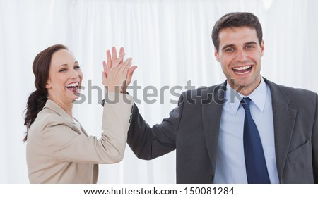 Cheerful workmates doing high five in bright office - stock photo