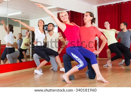 Cheerful young adults dancing pair dance in class. Selective focus - stock photo