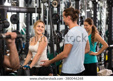 Cheerful young adults doing powerlifting on machines in modern fitness club