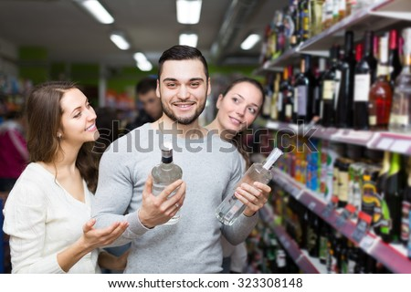 Cheerful young adults with bottles of vodka at supermarket. Focus on guy  - stock photo