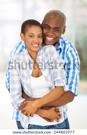cheerful young african american couple hugging each other indoors