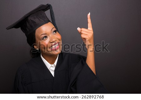 cheerful young african american graduate pointing up on black background - stock photo