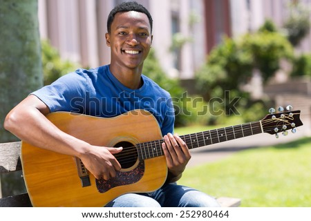 cheerful young african american man playing guitar outdoors - stock photo