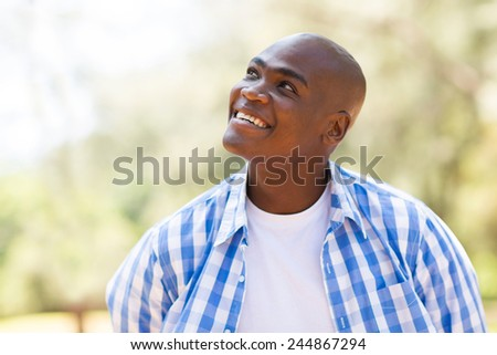 cheerful young african man looking up - stock photo