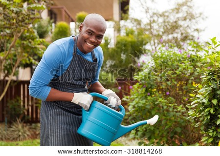 cheerful young african man watering plants - stock photo