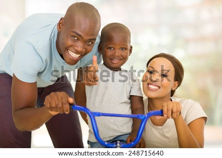 cheerful young african parents helping son to ride a bicycle indoors - stock photo
