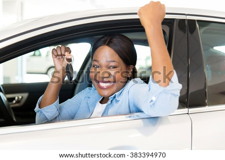 cheerful young african woman showing her new car key at dealership - stock photo