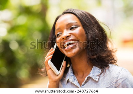 cheerful young african woman talking on smart phone - stock photo