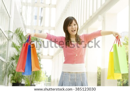 Cheerful young Asian woman with shopping bags walking out the mall. Beautiful golden sunlight background.